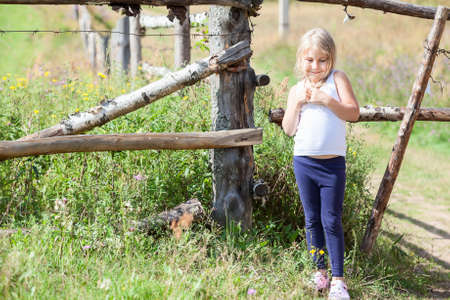 white singlet: Shy beautiful little girl in white singlet standing close to fence at summer. Copyspace Stock Photo
