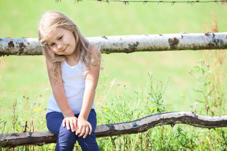 Embarrassed small girl sitting on rural fence. Copyspace photo