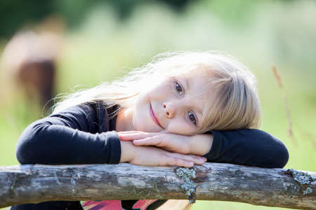 Blond hair girl with clasped hands resting in summer sunny day photo