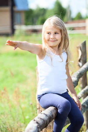 Beautiful smiling girl pointing far away sitting on rural fence photo