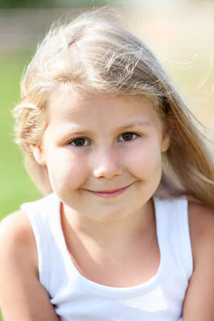Close-up portrait of happy small Caucasian girl with blond hair photo