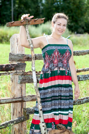peasant: Countrywoman standing with rakes behind fence in sundress in sunny summer day