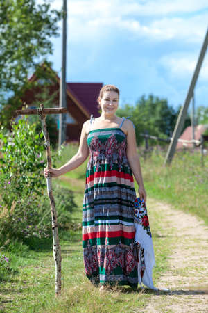 Countrywoman in village standing on rural road with working instruments photo