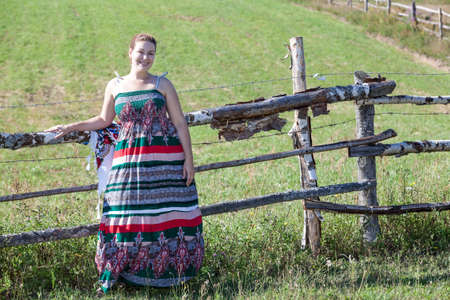 Countrywoman in sundress standing near village fence in field. Copyspace photo