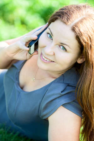 Beautiful Caucasian young woman portrait speaking on phone photo