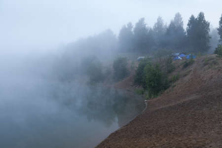 Fog on the lake with standing tourist tents at early morning photo
