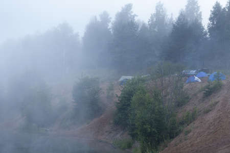 Fog on forest lake with standing tourist tents at early morning photo