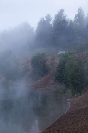 Foggy morning on forest lake with standing tourist tents on bank photo