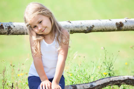 Embarrassed Caucasian small girl sitting on rural fence. Copyspace photo