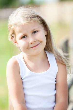 Half-length portrait of beautiful smiling girl with blond hair outdoors photo