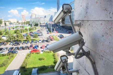 Video surveillance cameras on a wall looking at street parking area Standard-Bild