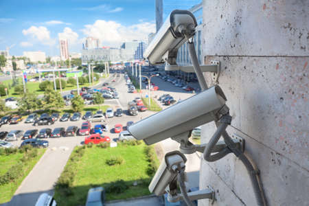 Video surveillance cameras on a wall looking at street parking area Stock Photo