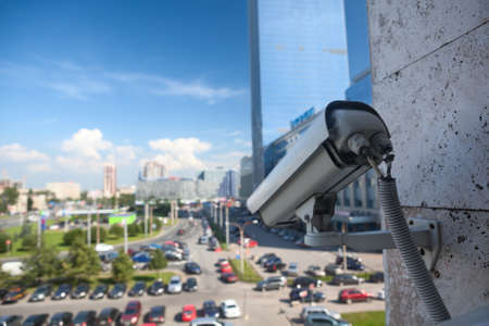 video cables: Video surveillance camera on a wall looking at street parking zone Stock Photo