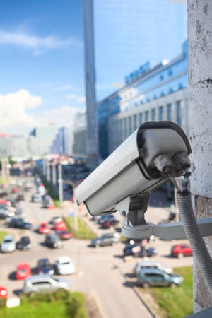 Video surveillance camera on a wall looking at city street photo