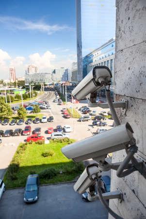 Video surveillance camera's op de bouw muur te kijken naar straat parkeren zone