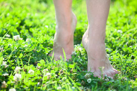 Front close-up view of female legs stepping on green grass Standard-Bild
