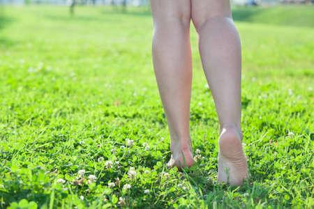 Walking barefoot on green grass women legs. Copyspace