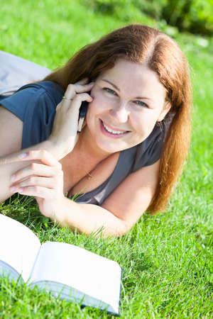 Happy smiling Caucasian young woman with book and phone laying on green grass photo