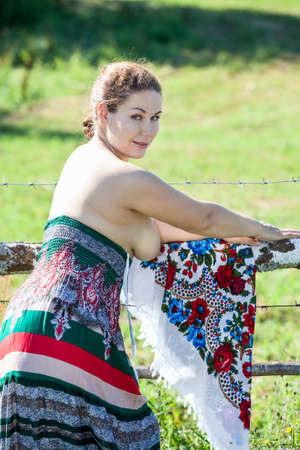 Woman with naked breast standing near the fence in the countryside Stock Photo