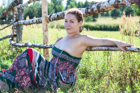 Woman with half-naked breast sitting near fence in field photo