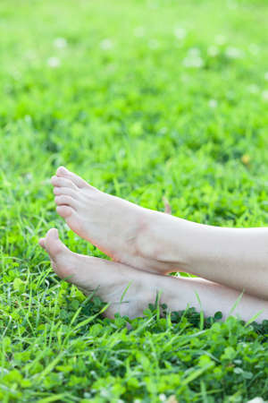 Barefooted attractive female feet laying in green grass photo