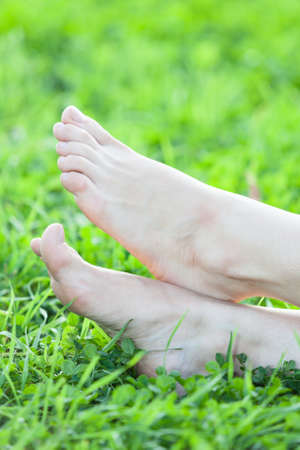 Barefooted female feet on grass vertical frame Stock Photo - 21512504