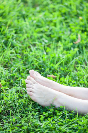 Barefooted attractive female legs laying in green grass vertical copyspace photo