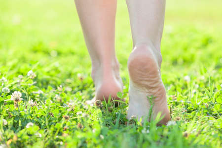 bare body women: Light step barefoot on the soft summer grass Stock Photo