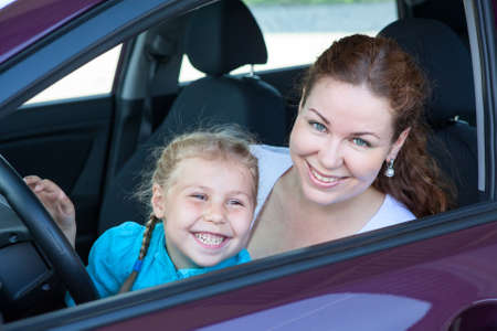 Happy toothy smiling mother with small daughter on driver seat inside of car photo