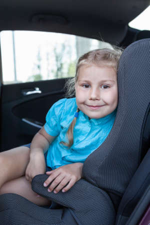 Pretty smiling child in car safety seat looking at camera photo