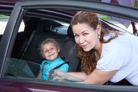Child sitting in baby car seat and mother helping photo