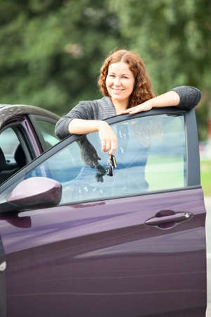 Beautiful bright brunette with keys standing near just bought car photo