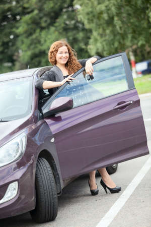 Laughing cheerful woman standing near new car with keys in hand photo