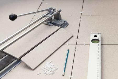 Kleine tegel-cutter met het leggen van tegels, potlood en niveau van de buis op de vloer