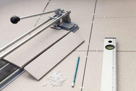 Small tile-cutter with laying tiles, pencil and level tube on floor