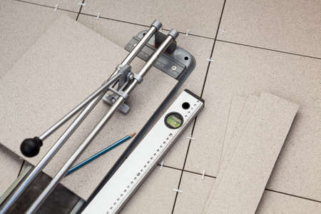 Construction tools as tiles cutter and level with pencil