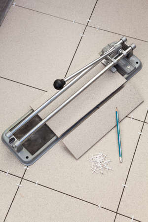 Tile-cutter with cutted tile on floor  photo