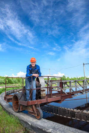 purification: Manual worker standing on waste water treatment unit on the industrial plant Stock Photo