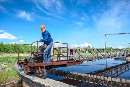 Senior engineer in bouwvakker die zich op de behandeling van afvalwater unit