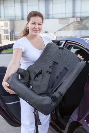 Young woman holding infant safety seat standing near car Stock Photo - 22218086