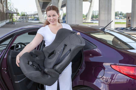 restraint: Mother holding infant restraint chair near own car Stock Photo