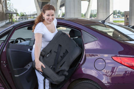 asiento coche: Mujer con asiento de la seguridad del bebé de colocarlo en el coche Foto de archivo