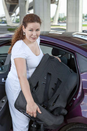 Young Caucasian woman with baby safety seat placing it in the car Stock Photo - 22218107