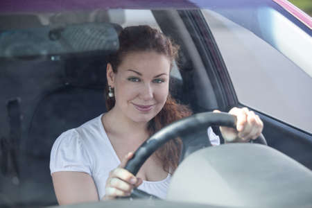Attractive young woman holding steering wheel and looking through the windscreen photo
