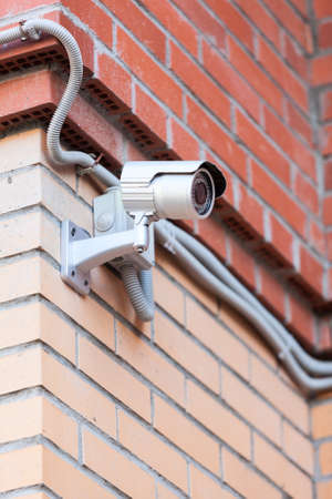Video surveillance camera on brick wall photo
