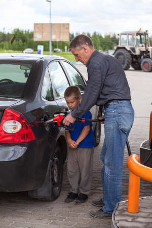 Father with son refueling car on gas station together photo