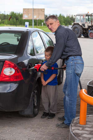 Senior grandfather with young boy refilling car at gas station photo