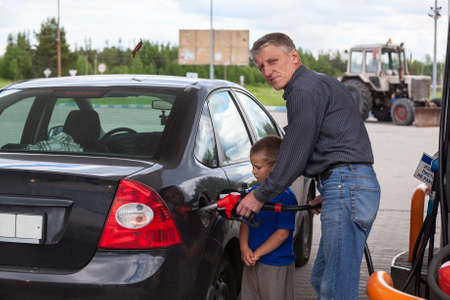 octane: Young son looking at father refilling car at gas station Stock Photo