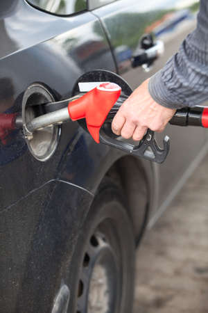 Male hand refilling the car with fuel on a filling station photo
