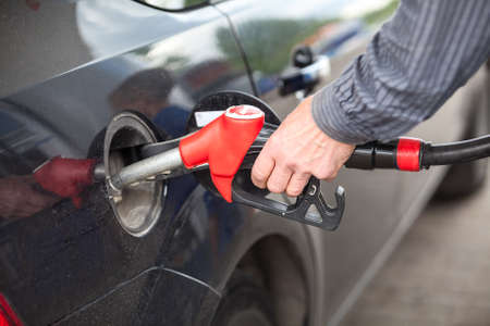 Driver inserting pumping nozzle with gasoline at the gas station photo